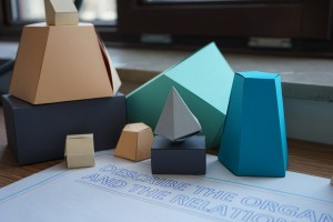 Focus on a part of the Visual Ideation Toolkit; some abstact shapes, folded from cardboard, are arranged in a small pile, on top of a sheet of paper used as a base. Some text is visible on the corner of the sheet.
