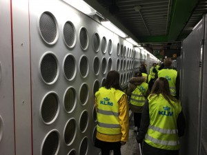 A group of people, wearing high-visibility jackets with the KLM logo, walking though a narrow, dimly-lit tunnel.